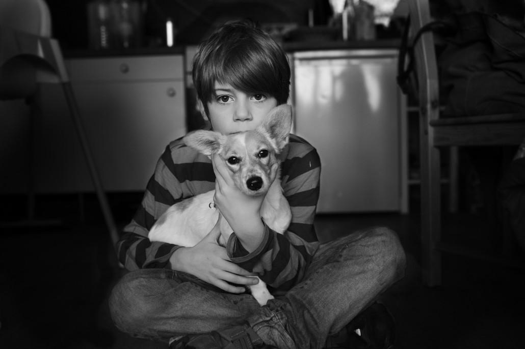 Junge und Hund sitzen am Boden Schwarz Weiss