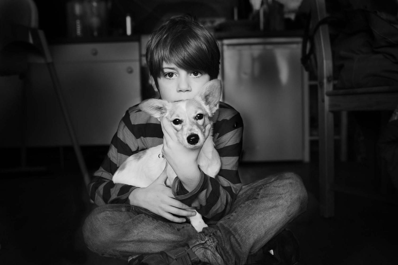 Junge hält Hund, auf dem Fussboden sitzend.