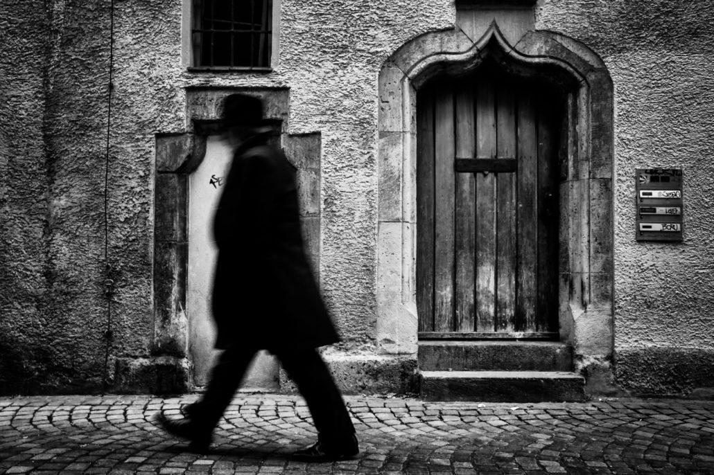 Schwarz-weisse Street-Fotografie eines vorbeigehenden Mannes vor einer Hausfassade.