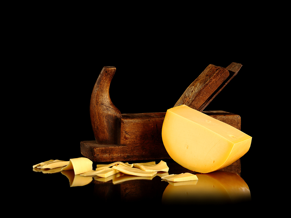 Fotografie eines Hobels mit einem Gouda-Käse