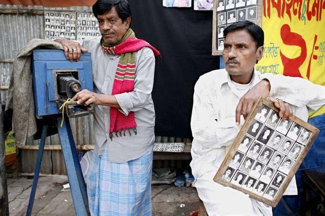 Safder Ali, der Porträtfotograf von Gullistan, Dhaka, und sein Assistent warten auf den nächsten Kunden. (Keystone / EPA / Abir Abdullah)