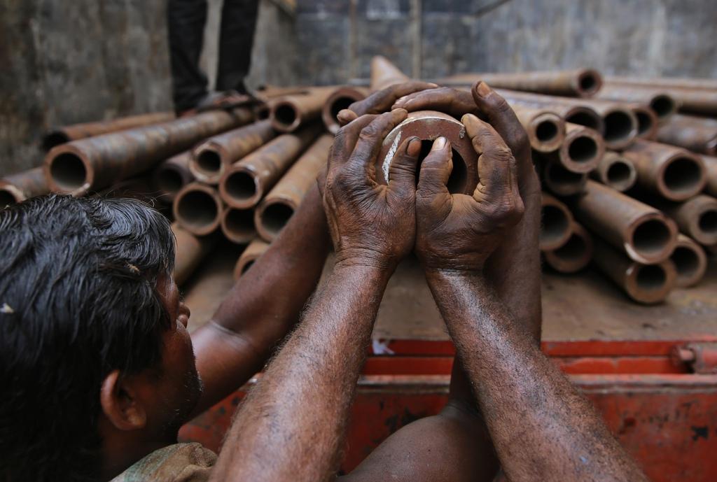 Arbeiten: Rohre verladen in Mumbai, Indien AP Photo/Rafiq Maqbool)