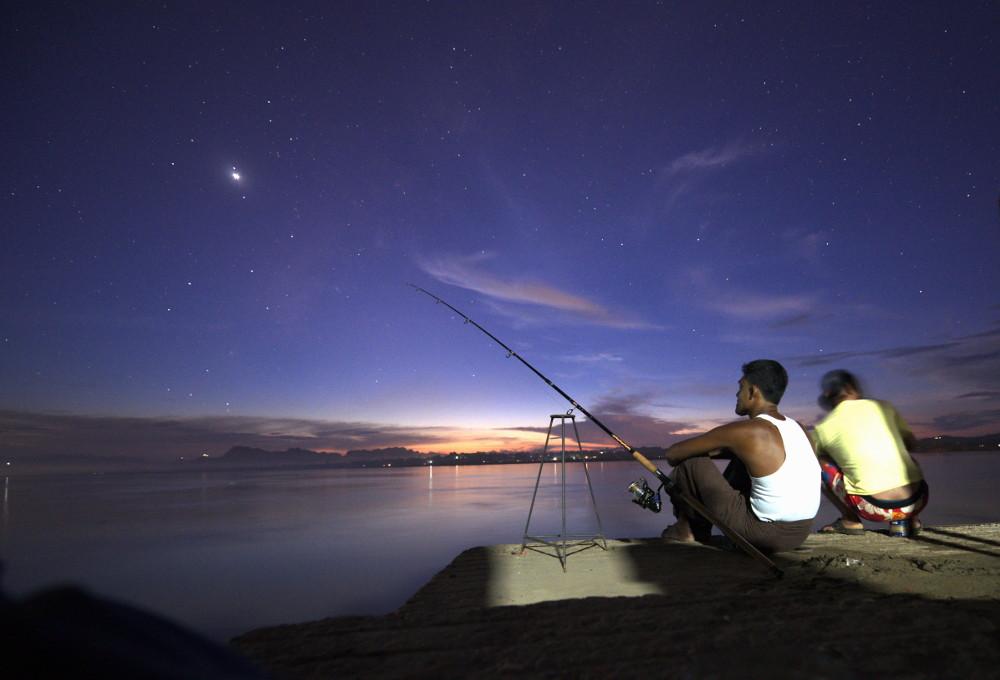 NAchtfotografie zweier Fischer am Ufer in Myanmar